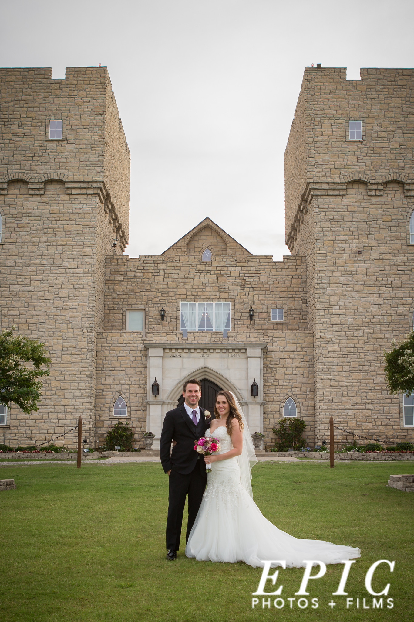 bride and groom posing for a photo on their wedding day in front of the stone-covered entrance to Castle at Rockwall