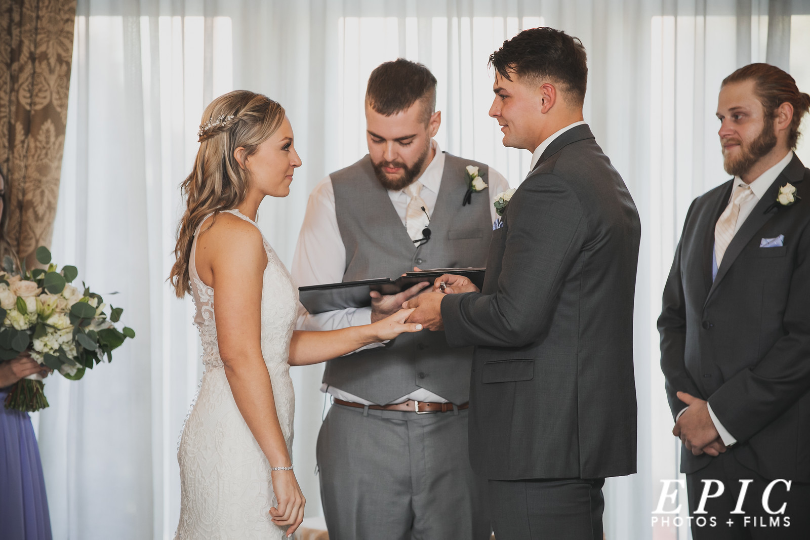 Groom putting ring on bride's finger during wedding ceremony at Loose Mansion