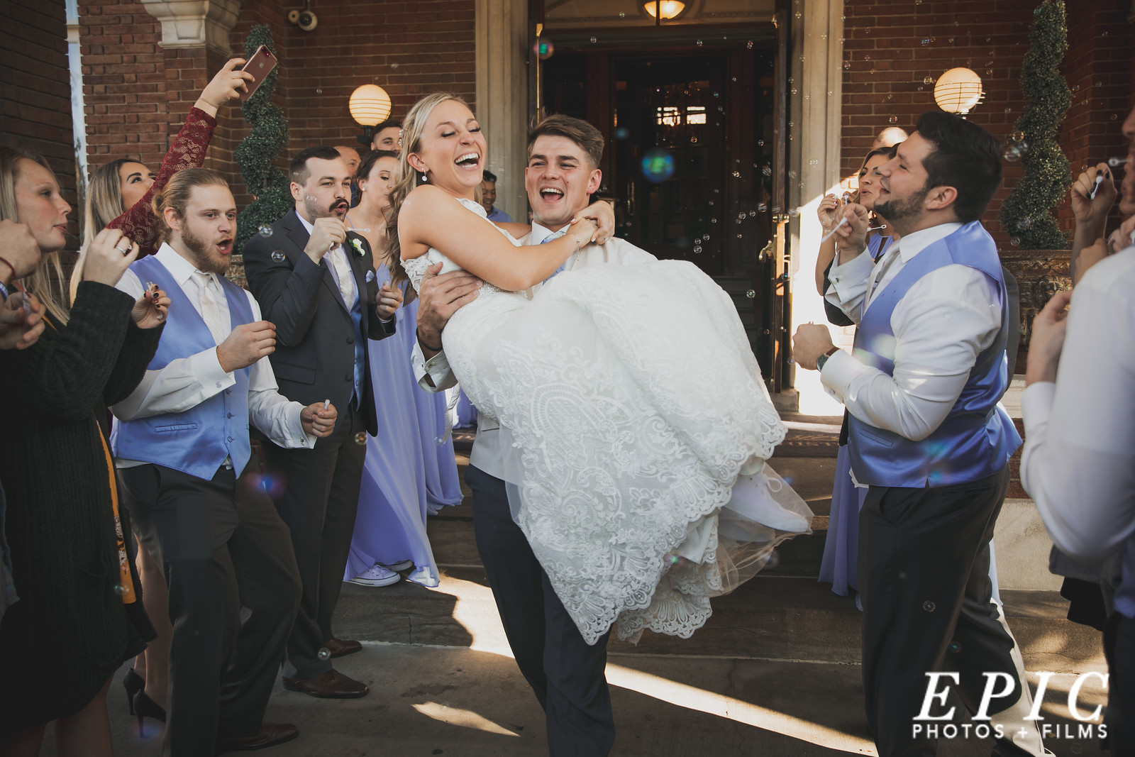 Bride and groom having a bubble exit as they exit their wedding reception surrounded by family and friends at Loose Mansion