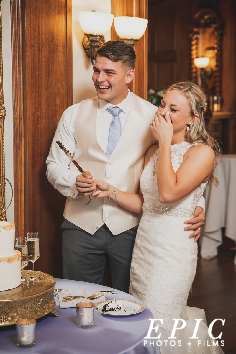 Bride and groom laughing while they cut their cake at Loose Mansion