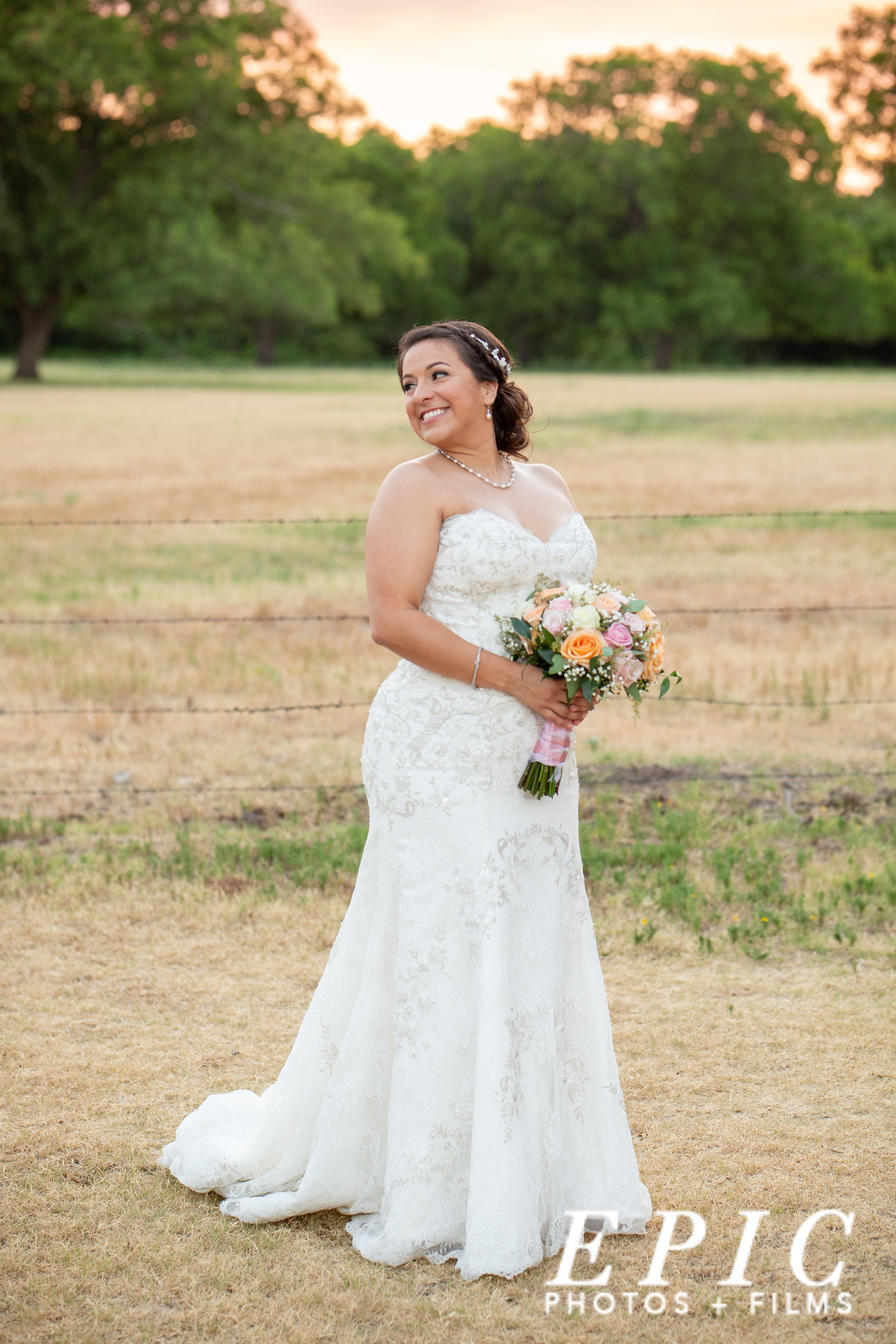 bride smiling behind her as she stands in a field near The Orchard at sundown on her wedding night