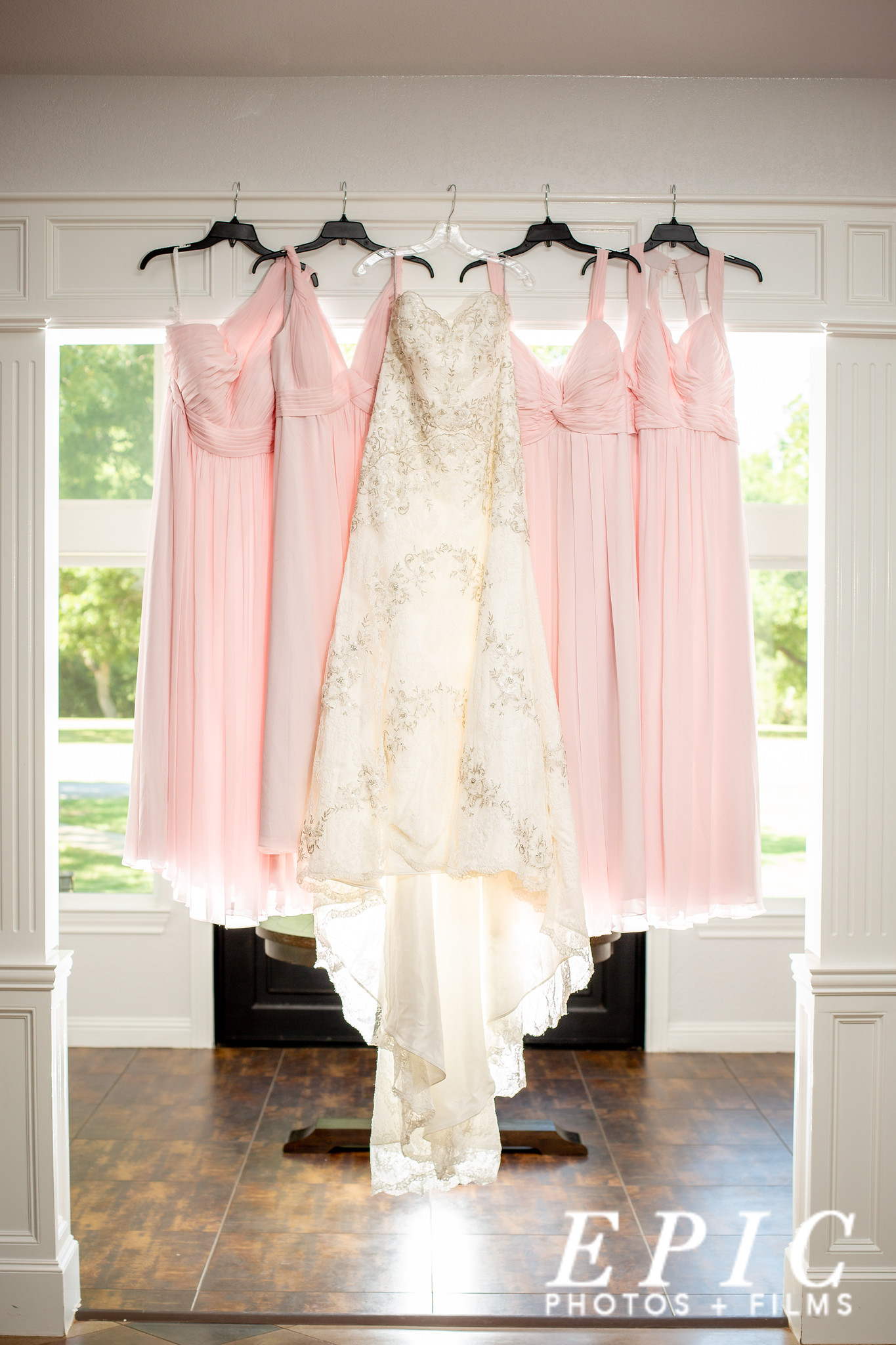 off-white lace wedding dress hanging next to four blush pink bridesmaids dresses on crown molding