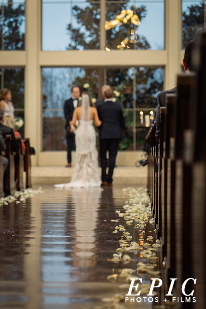 an artistic look down the aisle at the Chapel at Ana Villa lined with white flower petals with large uncovered windows