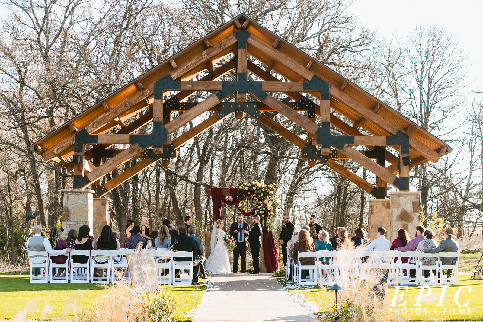 Hailee and Andrew standing under the pavilion during their ceremony outside