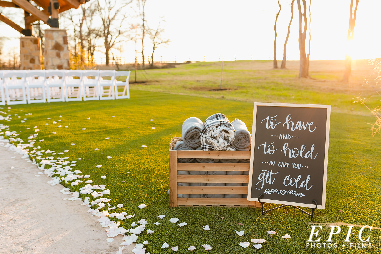 A basket of blankets with a and sign for wedding guest to keep warm during the ceremony