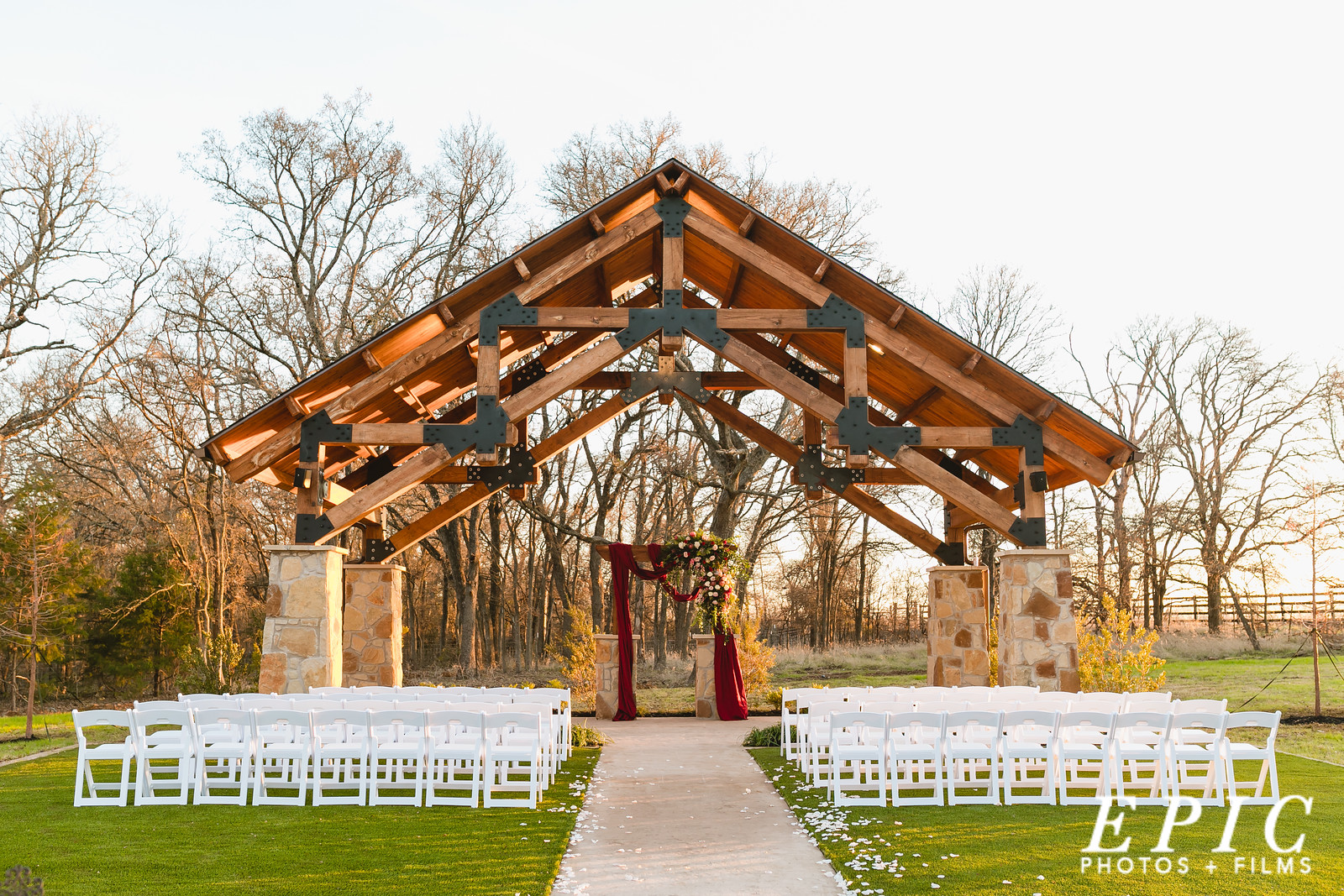 The outdoor ceremony location at The Springs Event Venue in Alvarado, Texas with floral and red drapes
