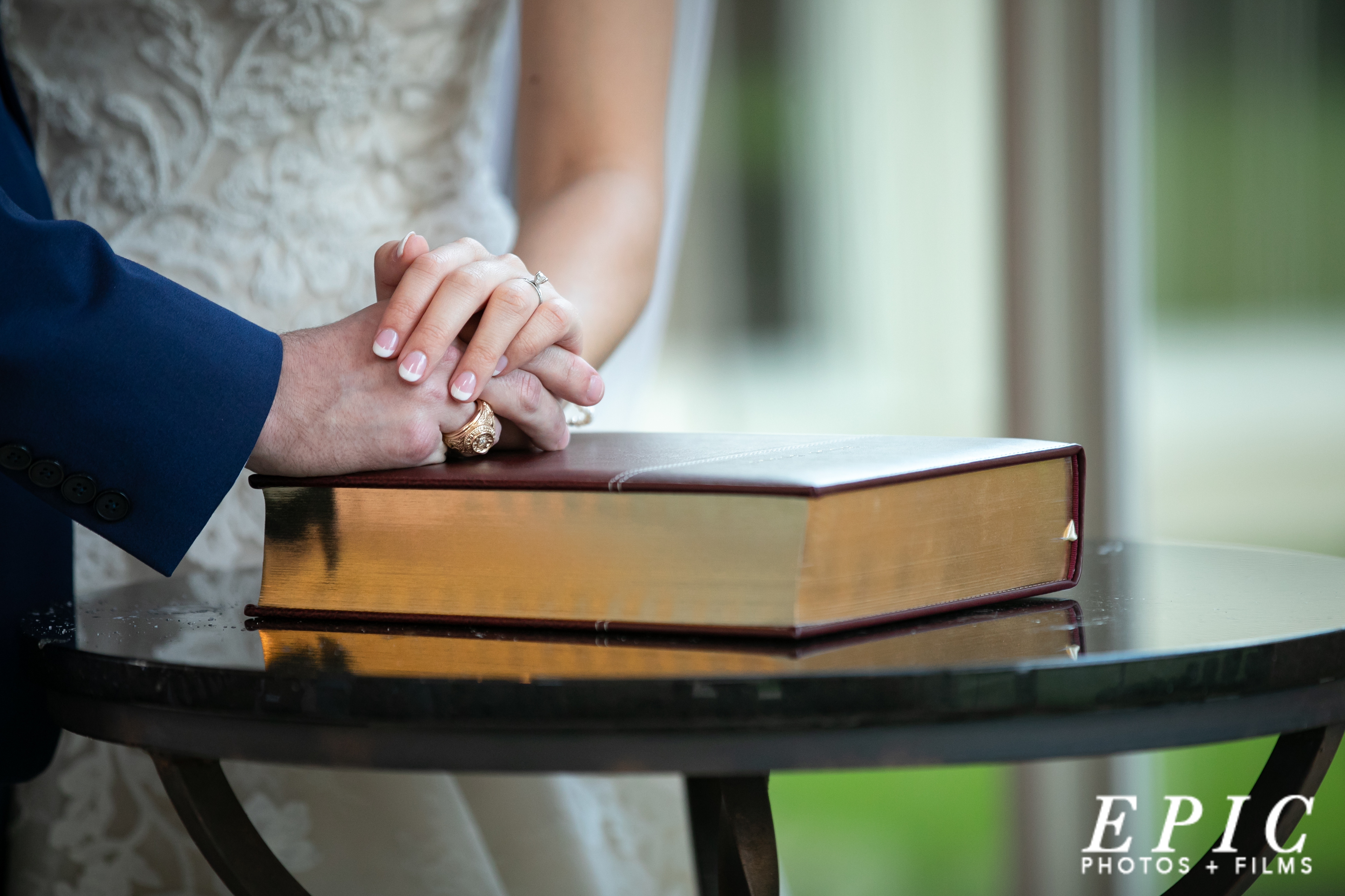 bride and groom standing holding one another as they place their hands on a bible