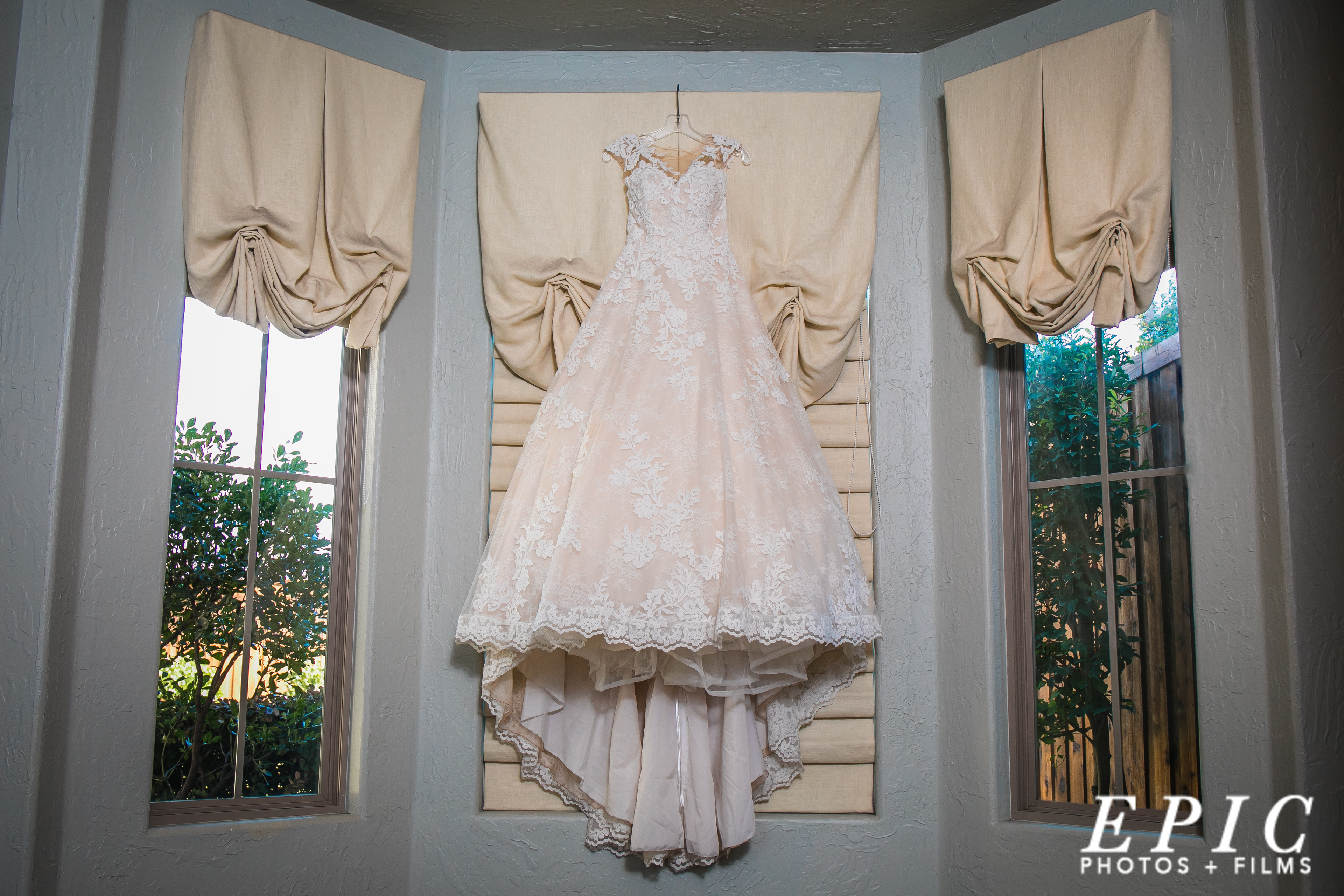 lace, off-white wedding dress haning from a window shade