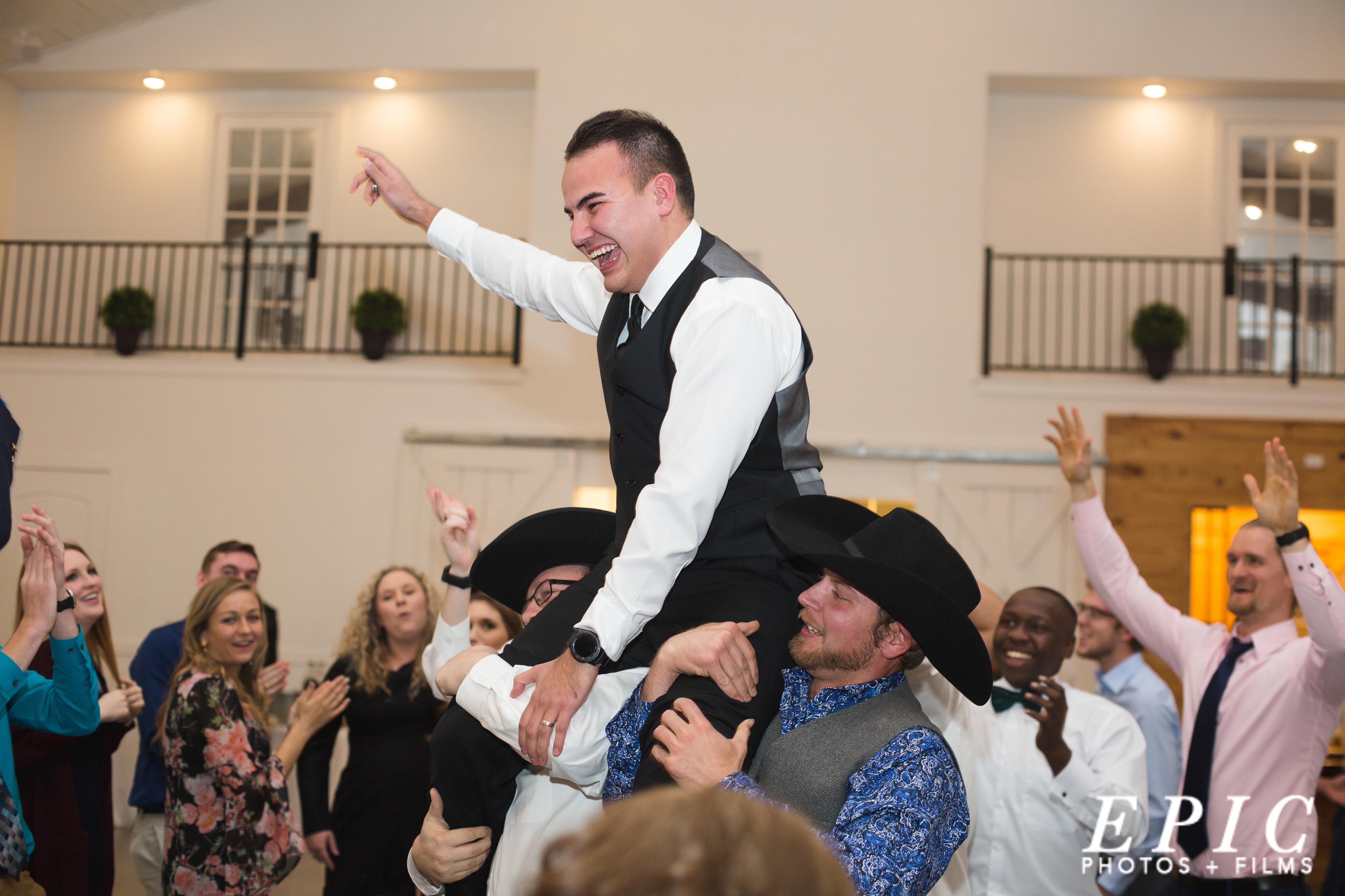 wedding guests carring the groom on their shoulders through a wedding reception