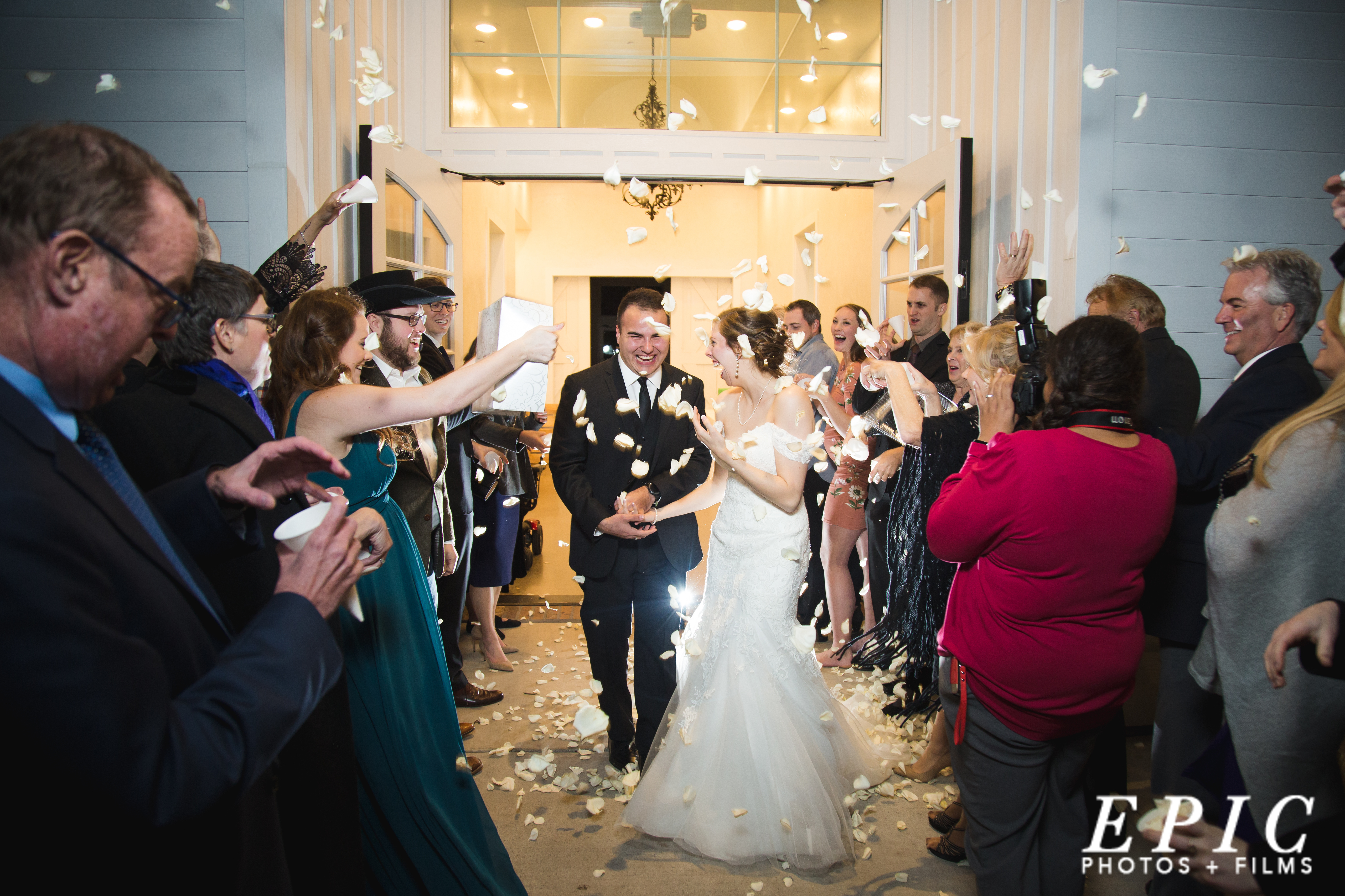 bride and groom being showered with white flower pedals during their grand exit from their wedding reception