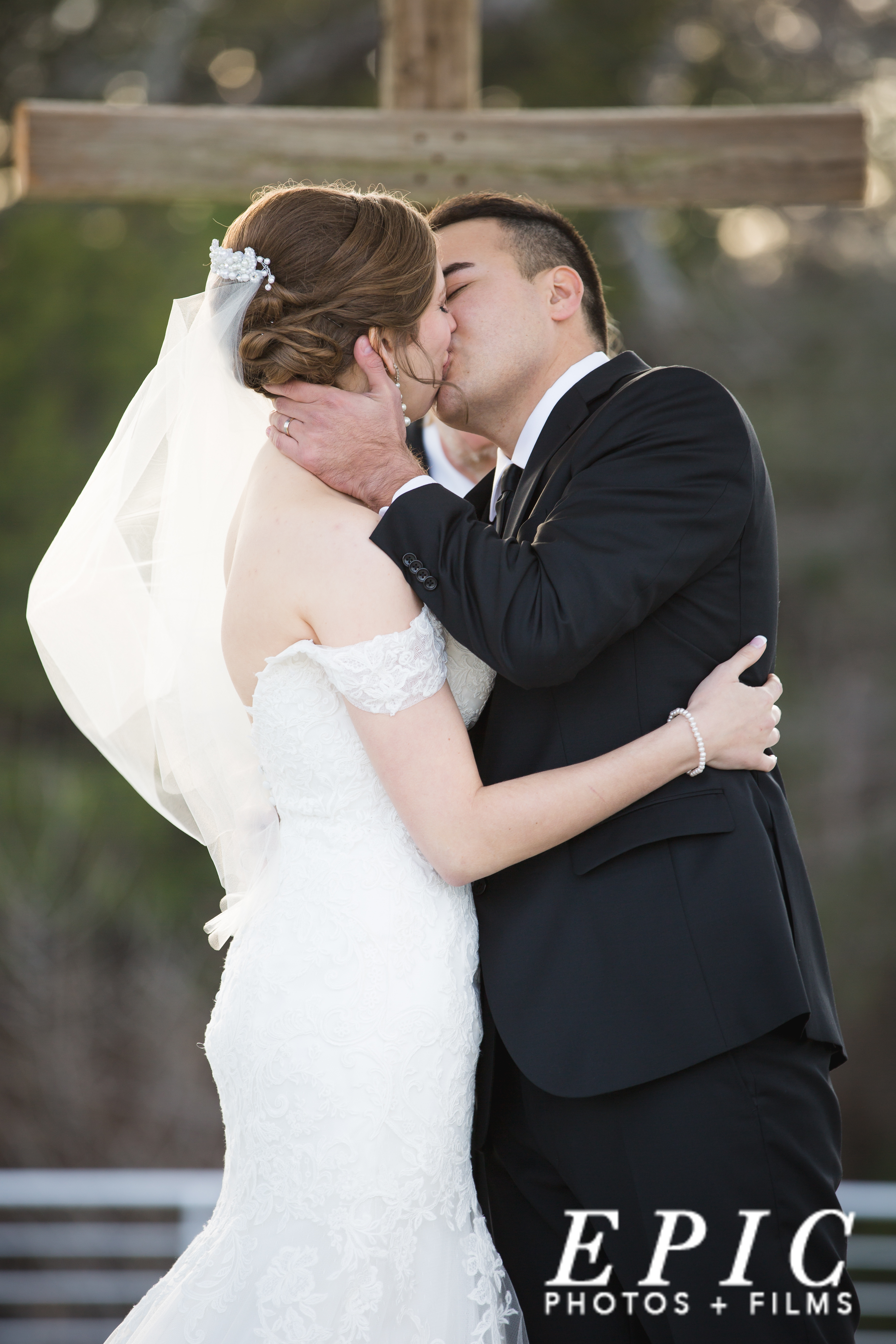 bride and groom kiss a they complete their vows to one another