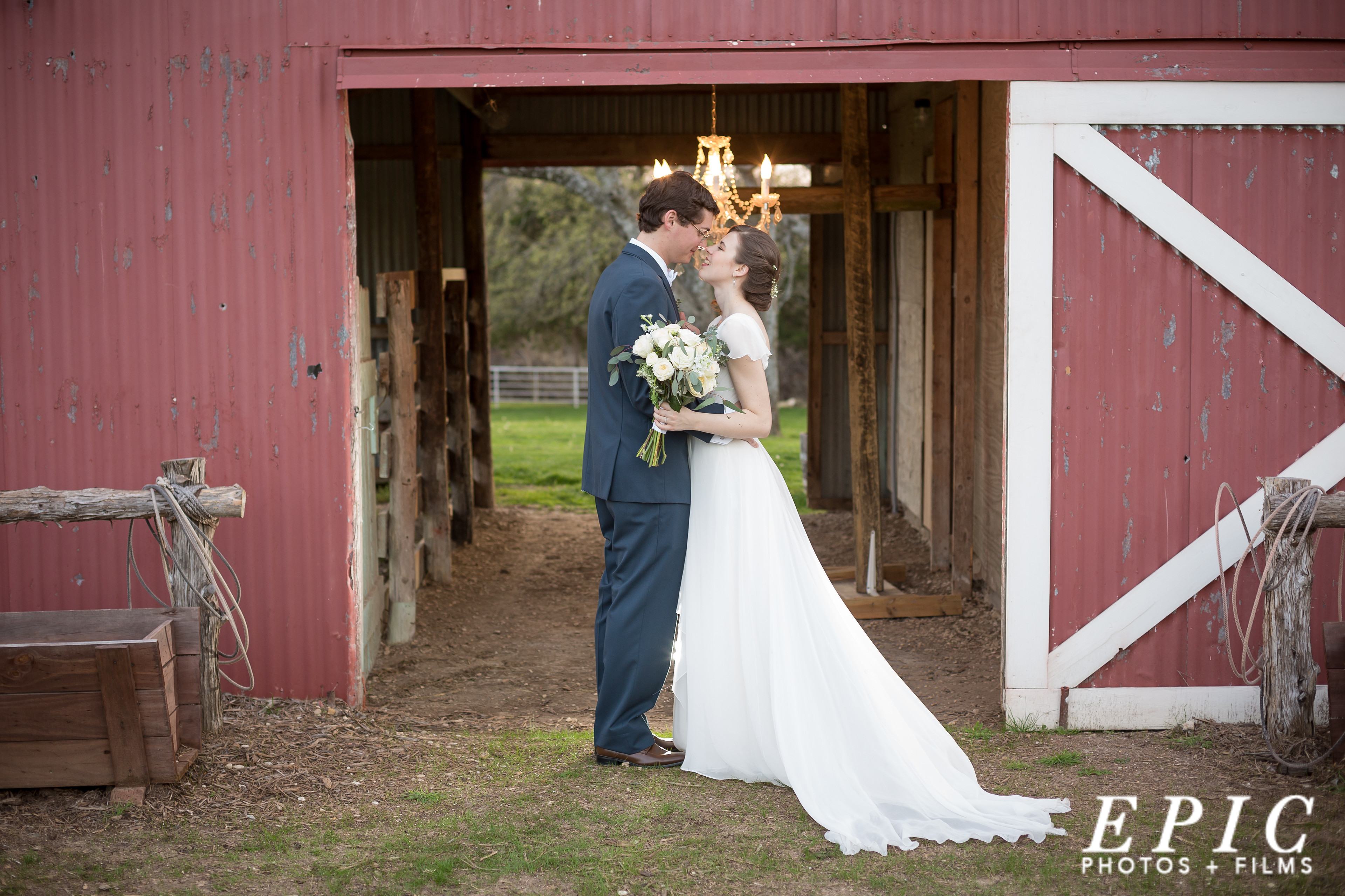 newlyweds touching noses in front of a red barn