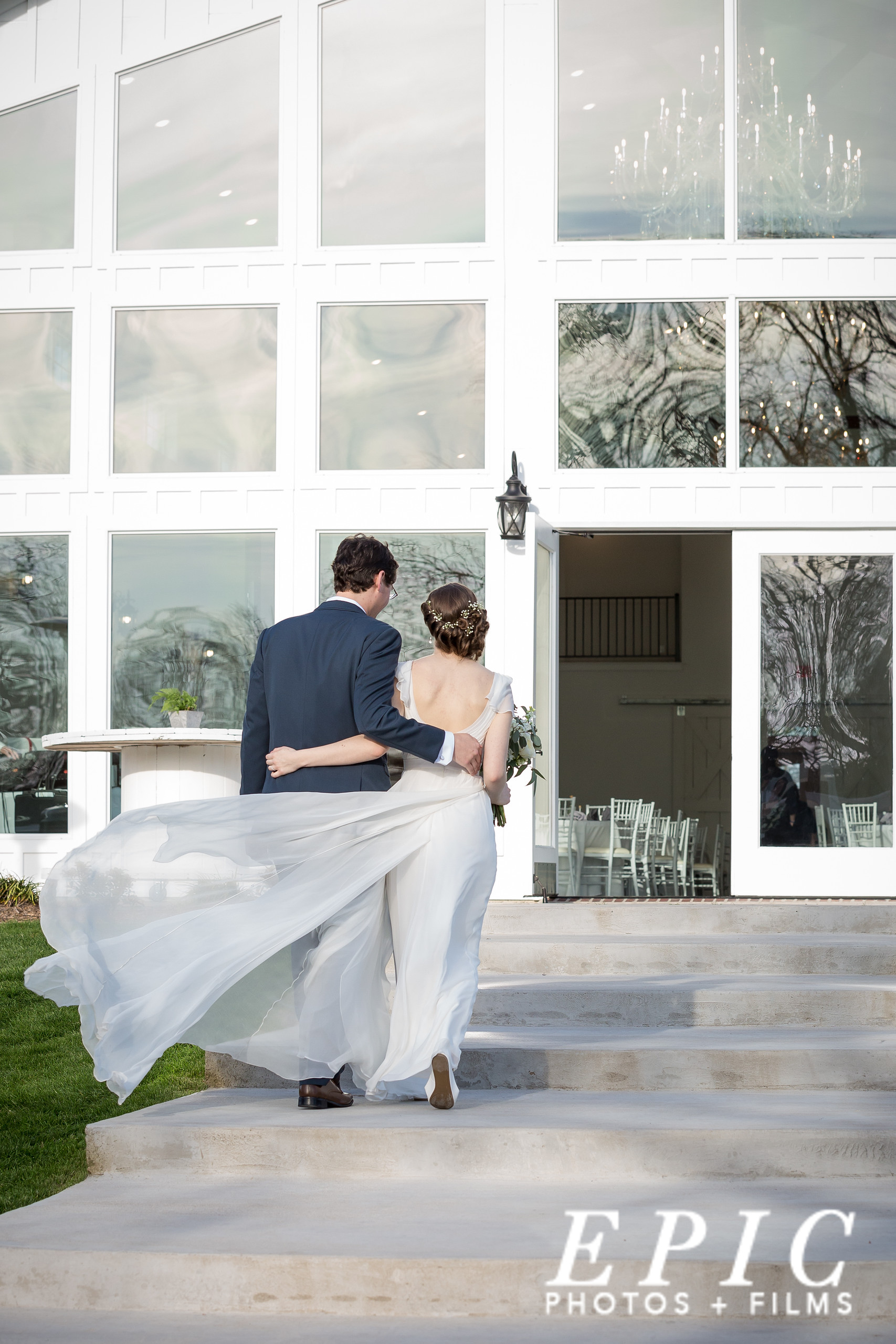 newlyweds walking into the large glass doors of Firefly Garden