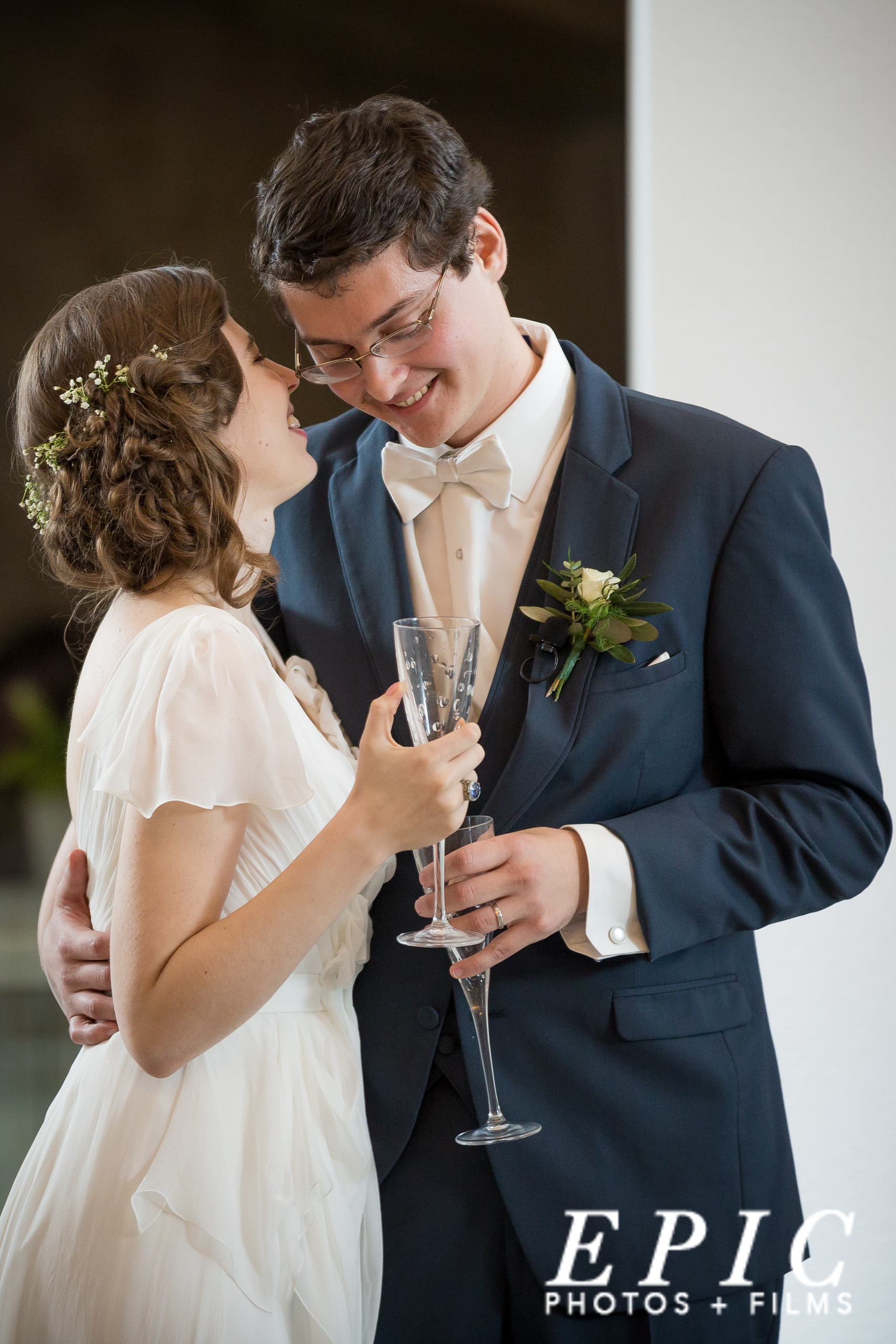 Bride whispering into her grooms ear as they toast champagne
