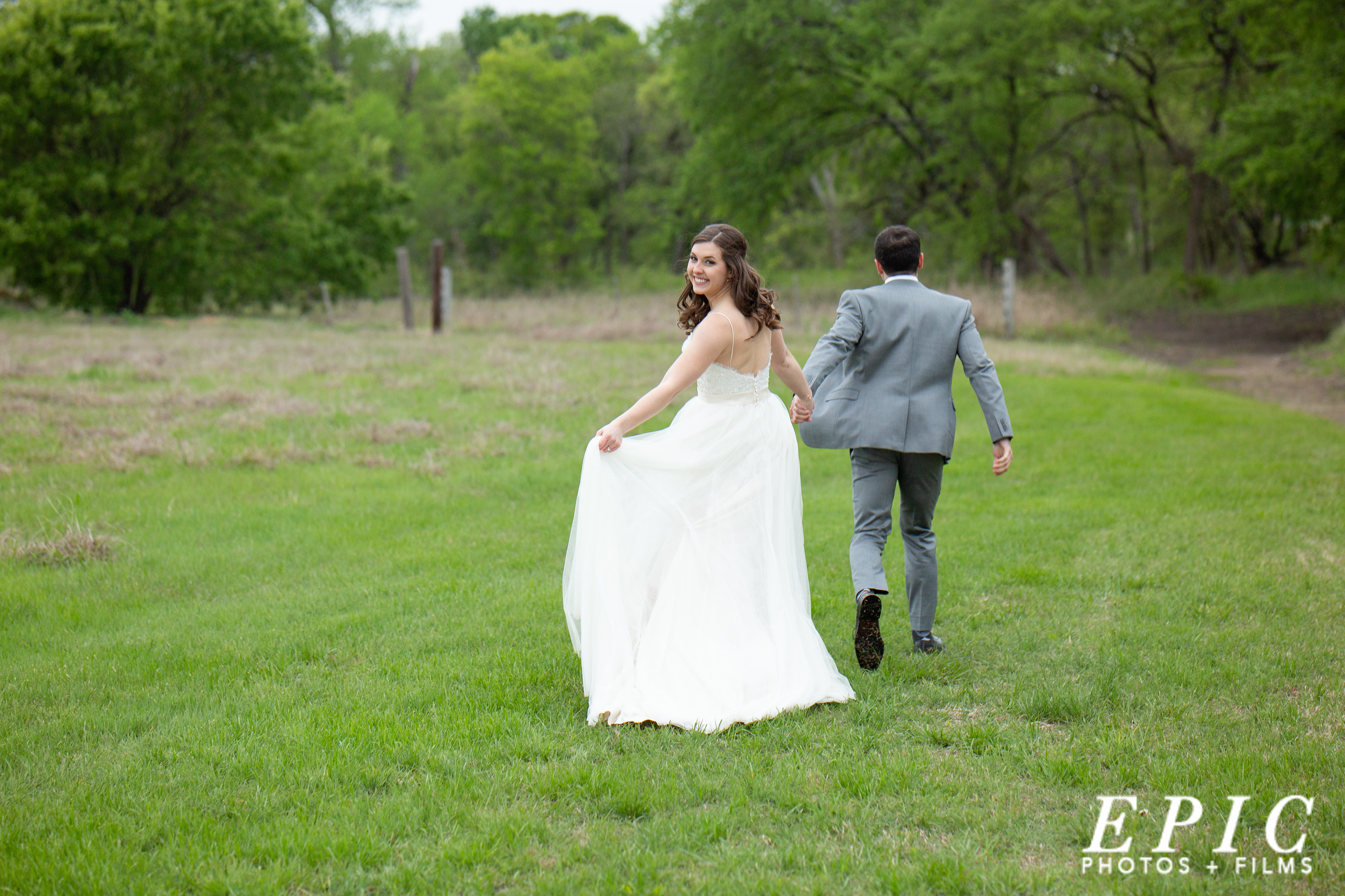 bride and groom run through a green grass field toward a wooded area just outside of their wedding venue