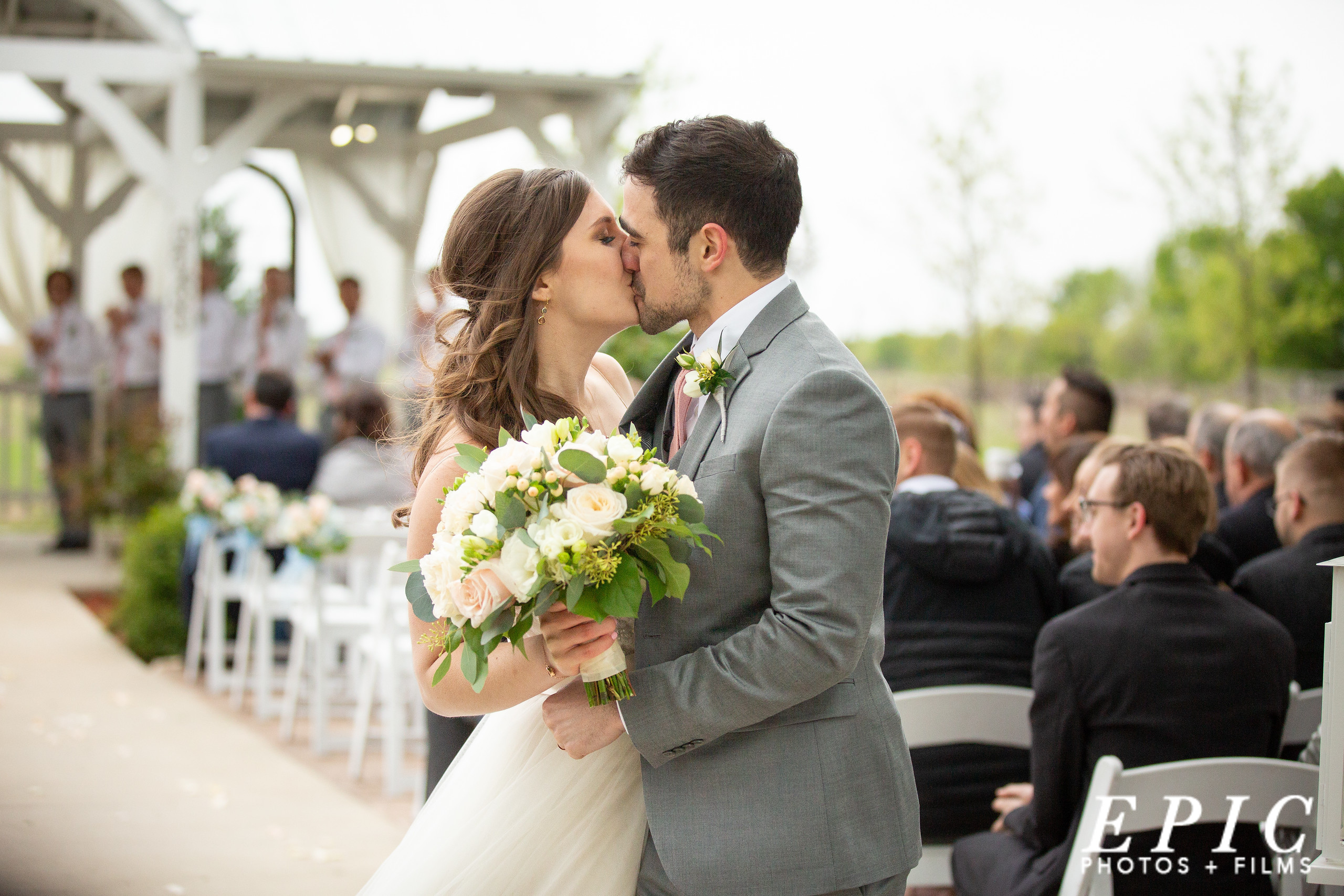 bride and groom kiss as they make it to the back of the seating area at Willow Creek as they finish their recessional walk down the aisle