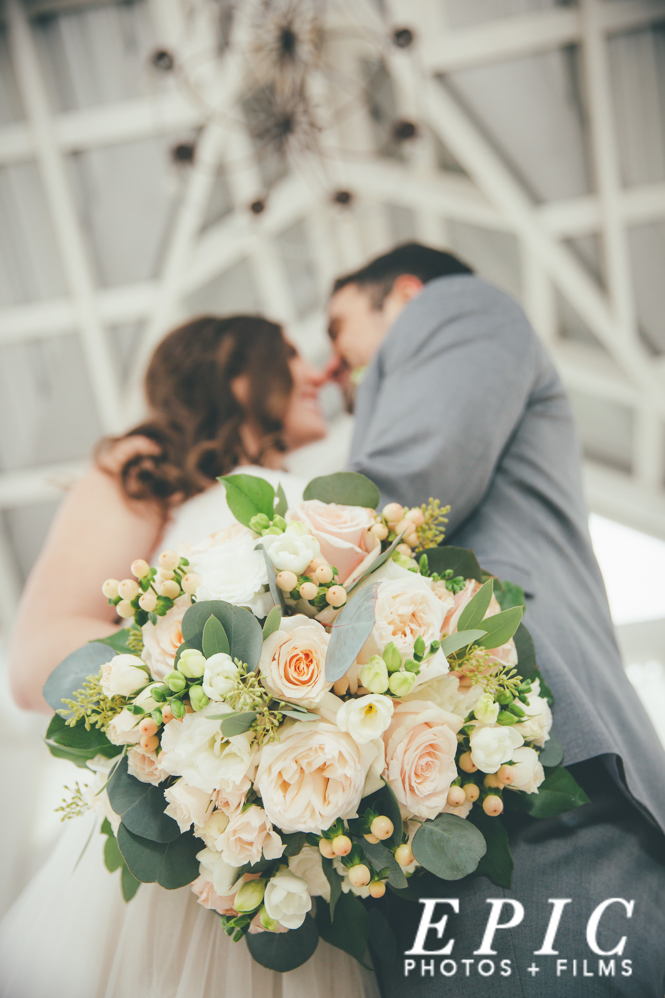 brides beige white and green bouquette, bride and groom touching noses in the blurred background