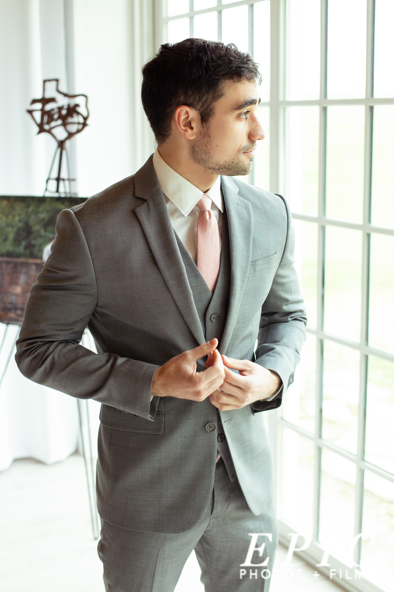 groon wearig a grey three piece suit looking out of a window before his wedding
