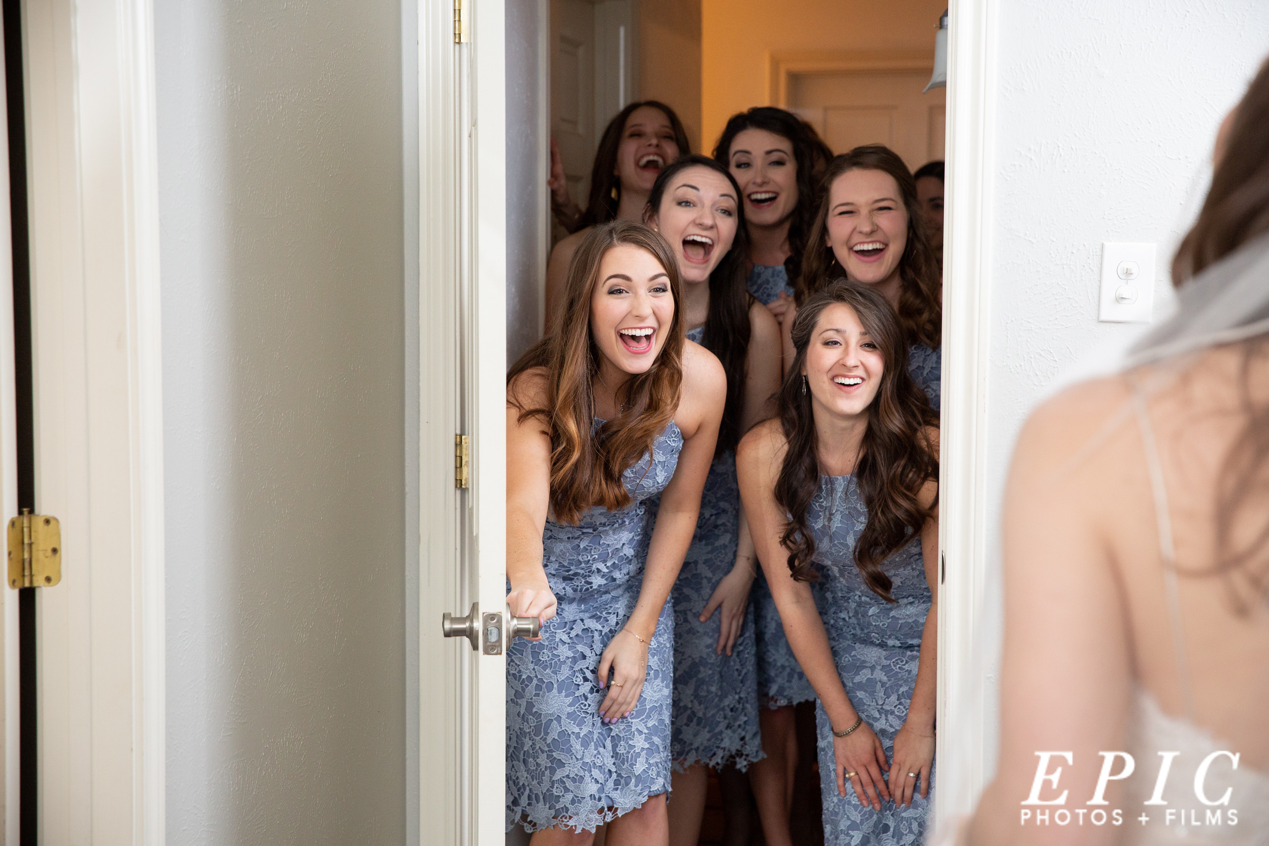 five bridesmaids walk into the dressing room at Willow Creek to find the bride as they all smile