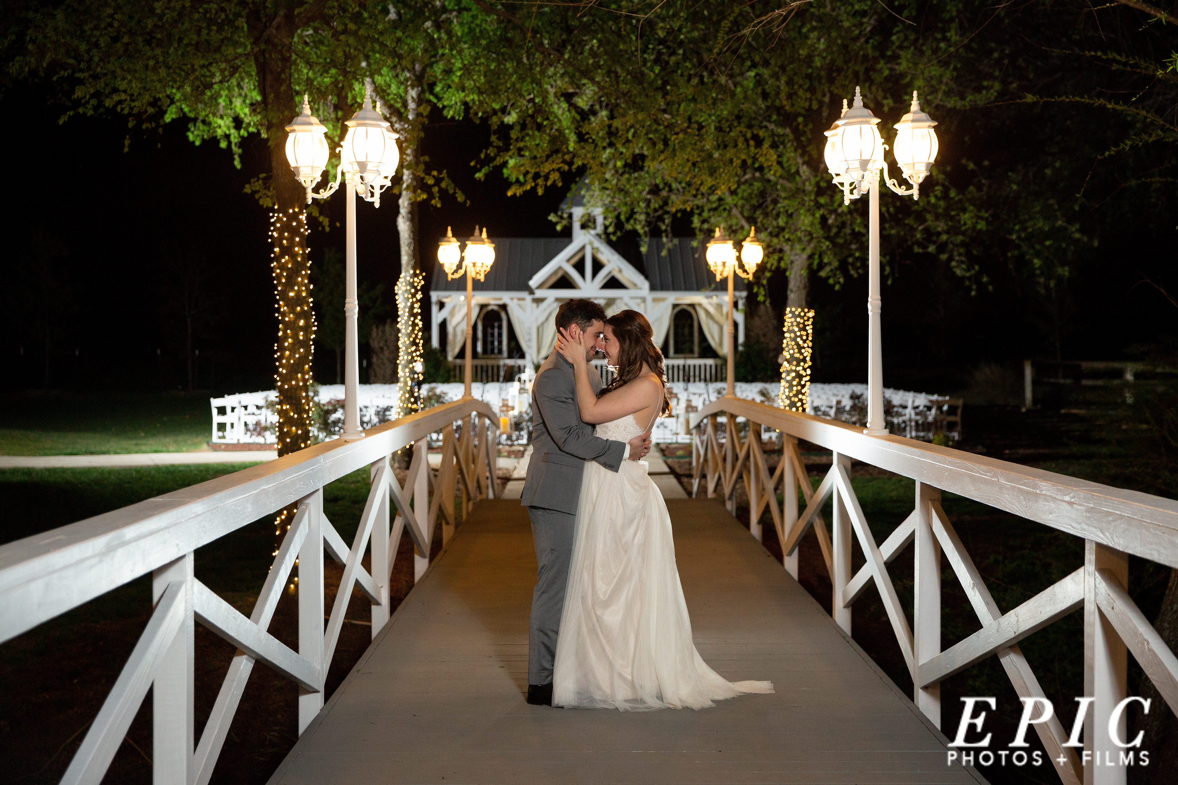 bride and groom stand on a white bridge at Willow Creek