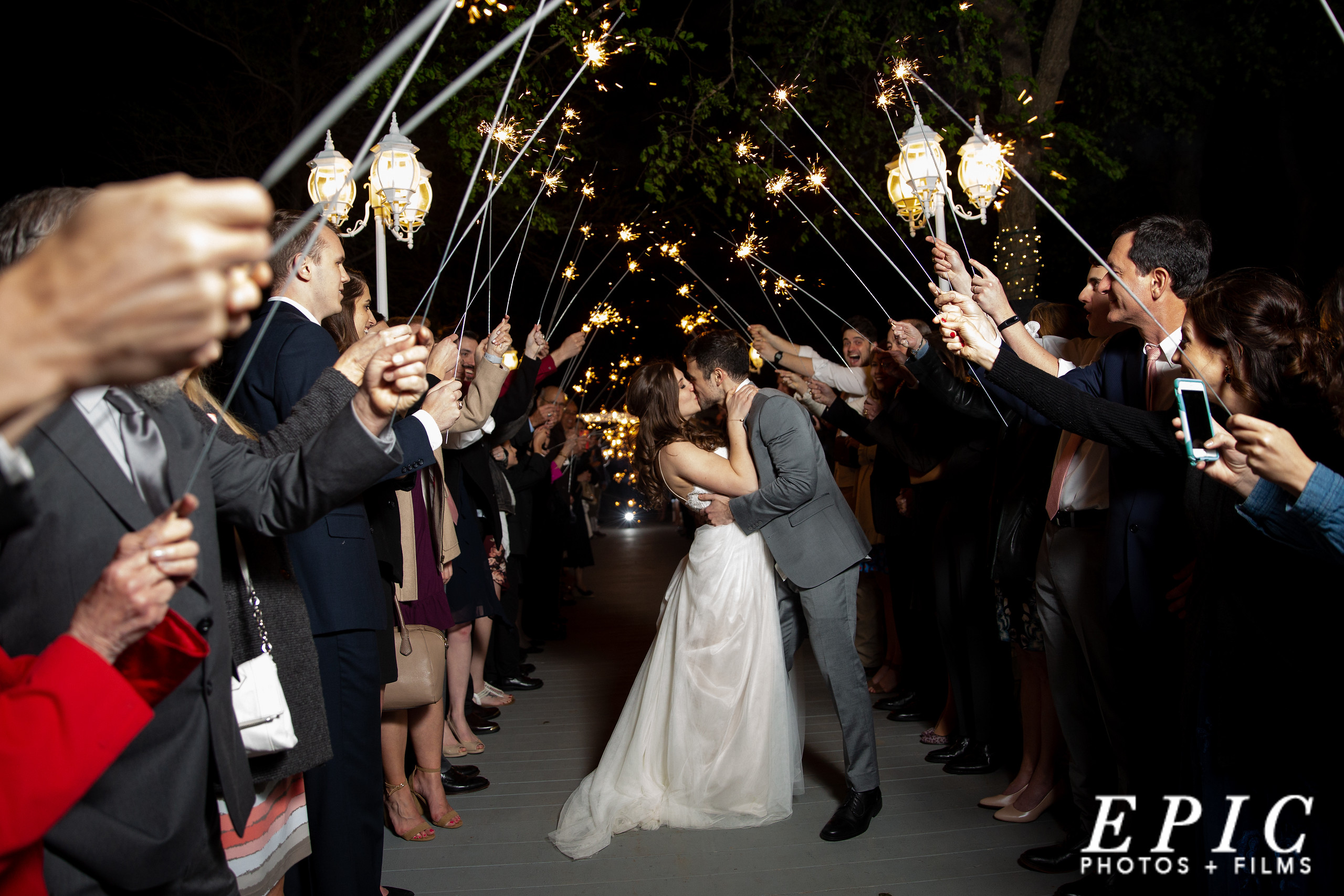 newlywed couple kissing as they are surrounded by their wedding guests holding sparklers as they leave the wedding reception in the grand exit