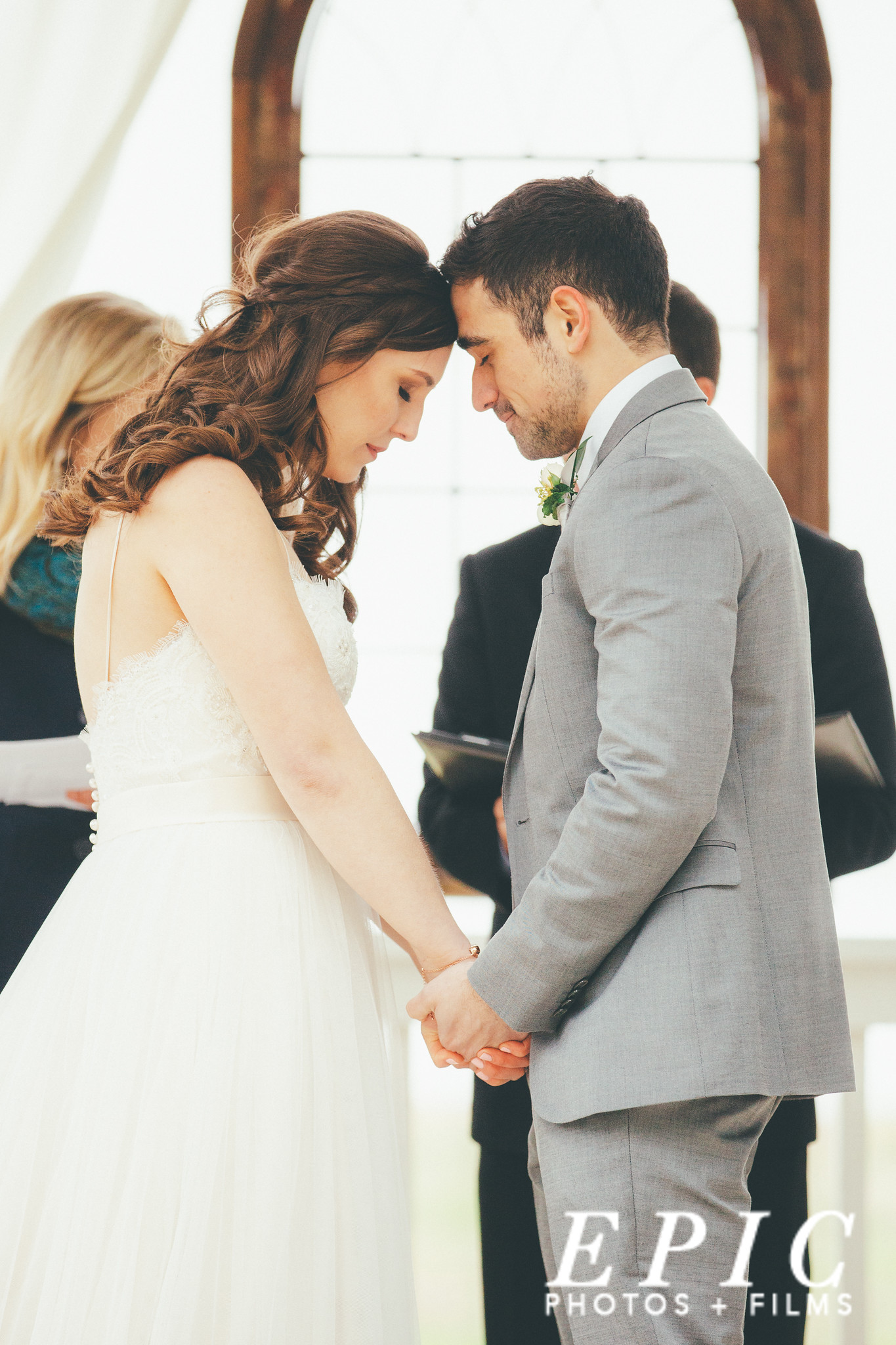 bride and groom stand holding hands with their foreheads touching and their eyes closed at the alter as they pray