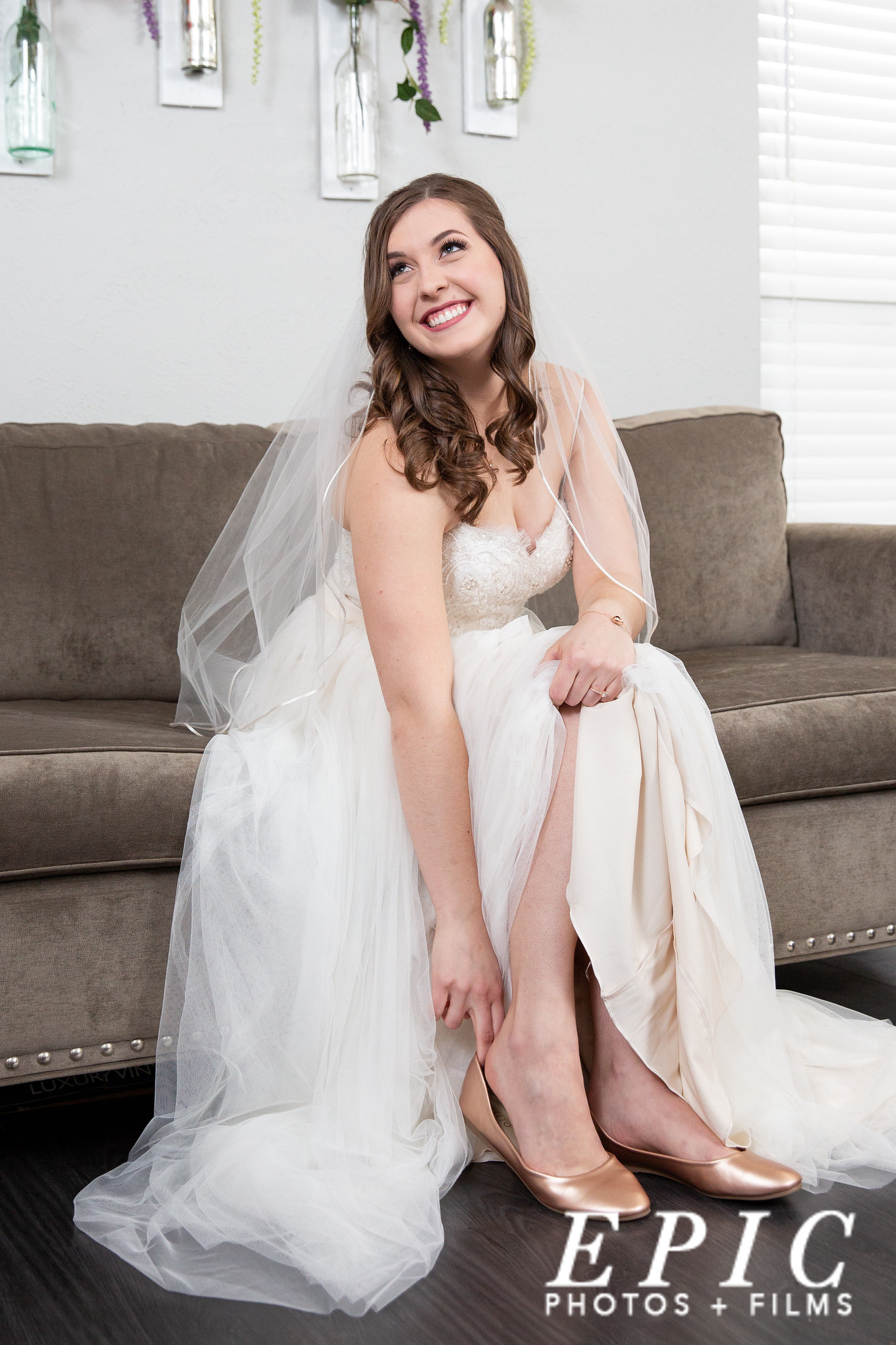 bride slipping her rose gold wedding flats on while smiling