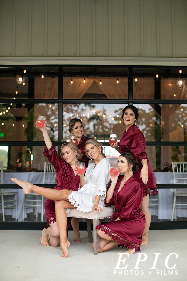 Bridemaids surrounding bride sitting in a chair all in matching robes cheersing with their personalized mimosa glasses at dream point ranch