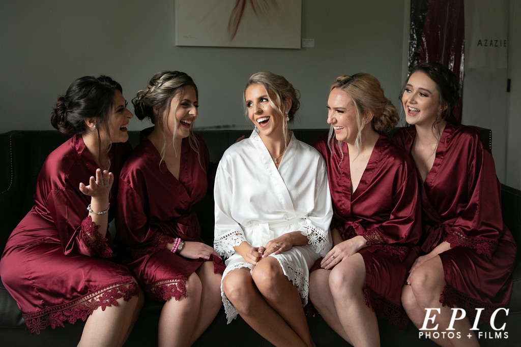 Bride and her bridesmaids sitting on couch laughing in the bridal suite at dream point ranch