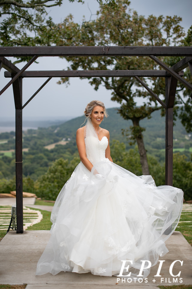 Bride swings her dress from side to side under a gazebo at dream point ranch