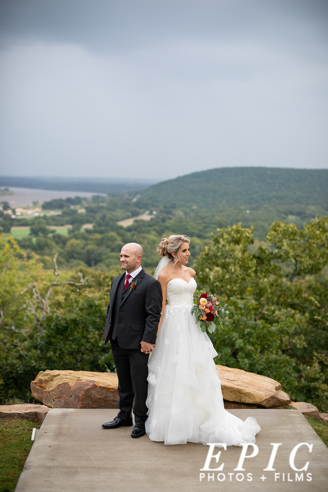 Bride and groom stand back to back posing in front of a hilltop view at dream point ranch