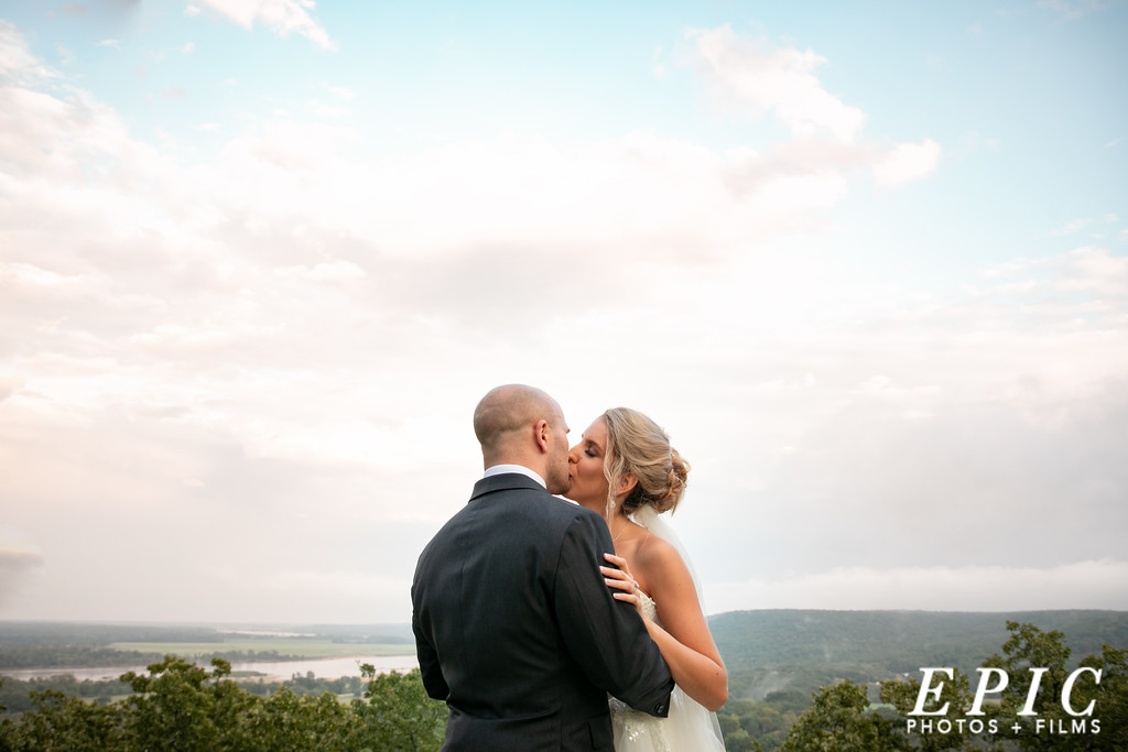 Bride and groom kiss in front of a clear blue sky with a hilltop view at dream point ranch