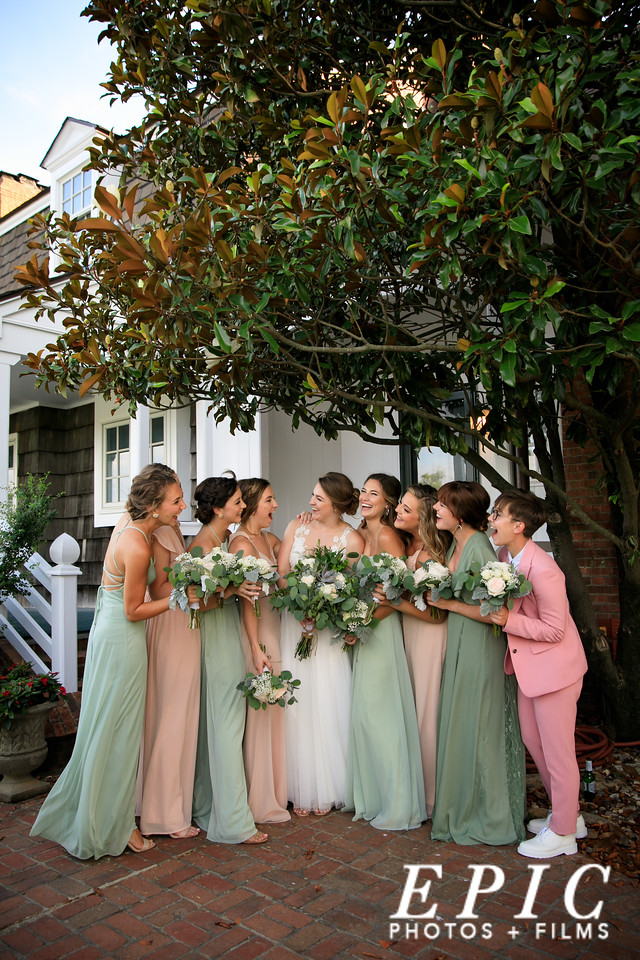 Bridal party surrounding bride and groom cheering during kiss at Loose Mansion