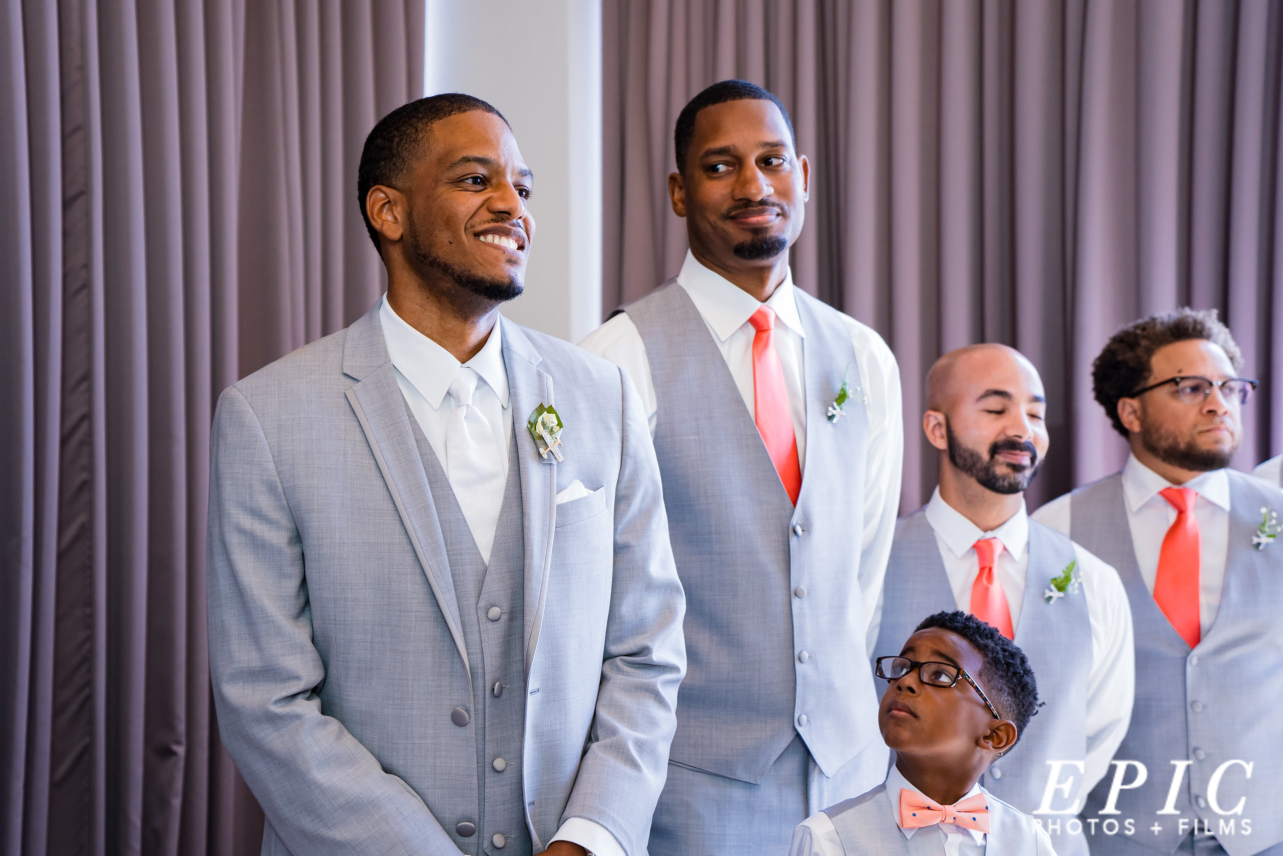 Groom smiling and looking down the aisle at The Orion Ballroom with his groomsmen standing at his side