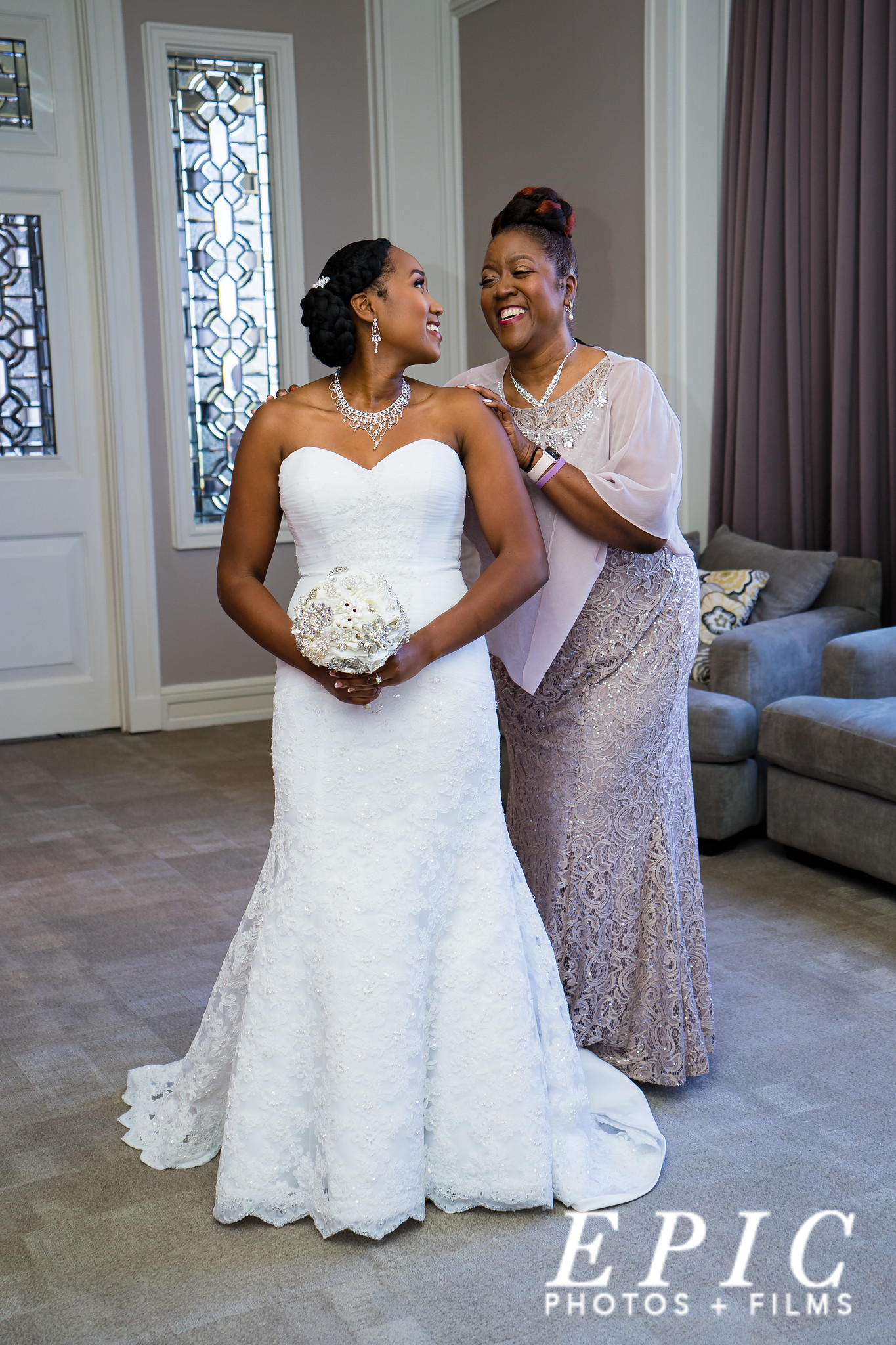 mother places her hands on her daughters shoulders as she gets ready for her wedding