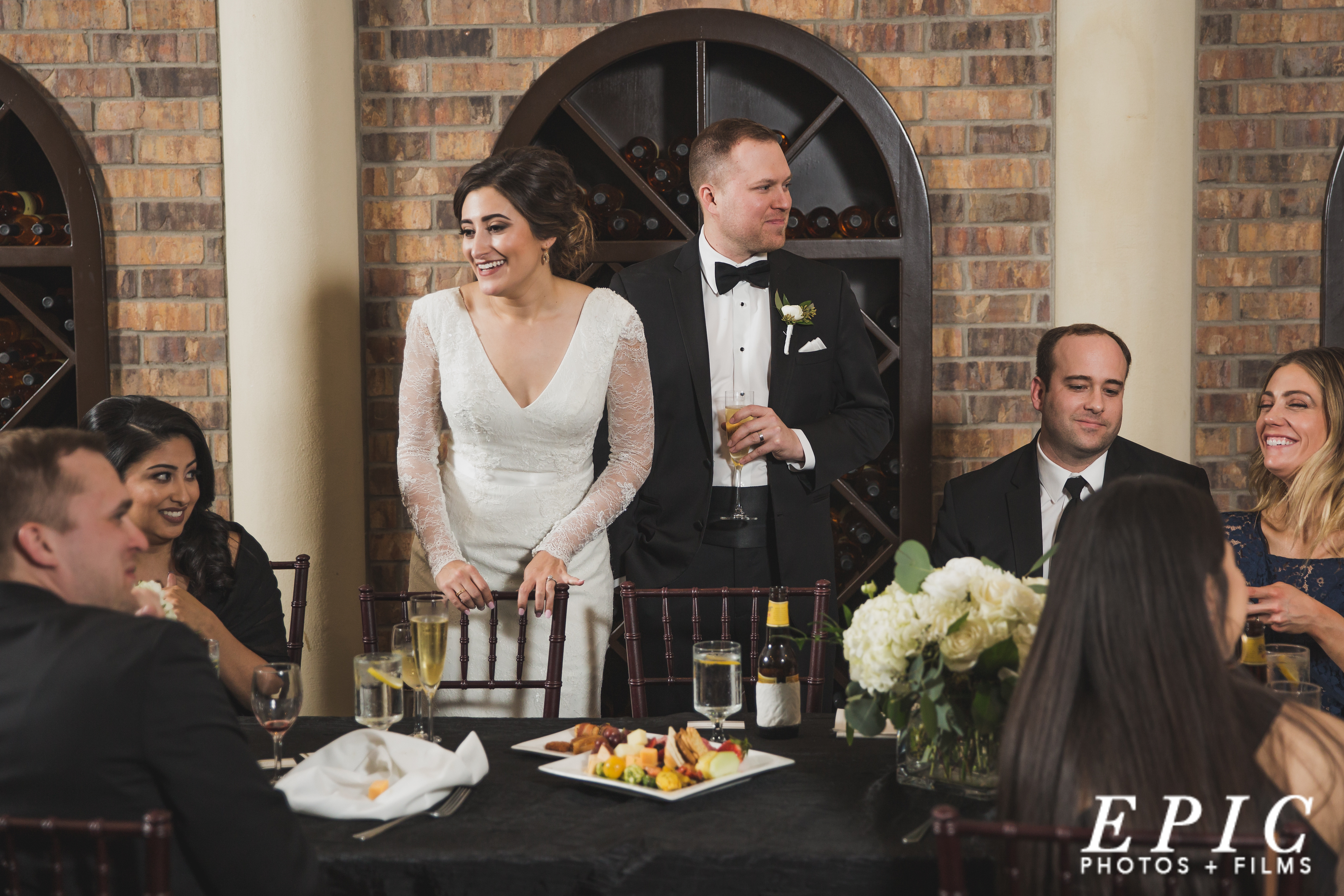 bride and groom stand of a toast behind their head table covered with a black table cloth and white flowers in glass vases