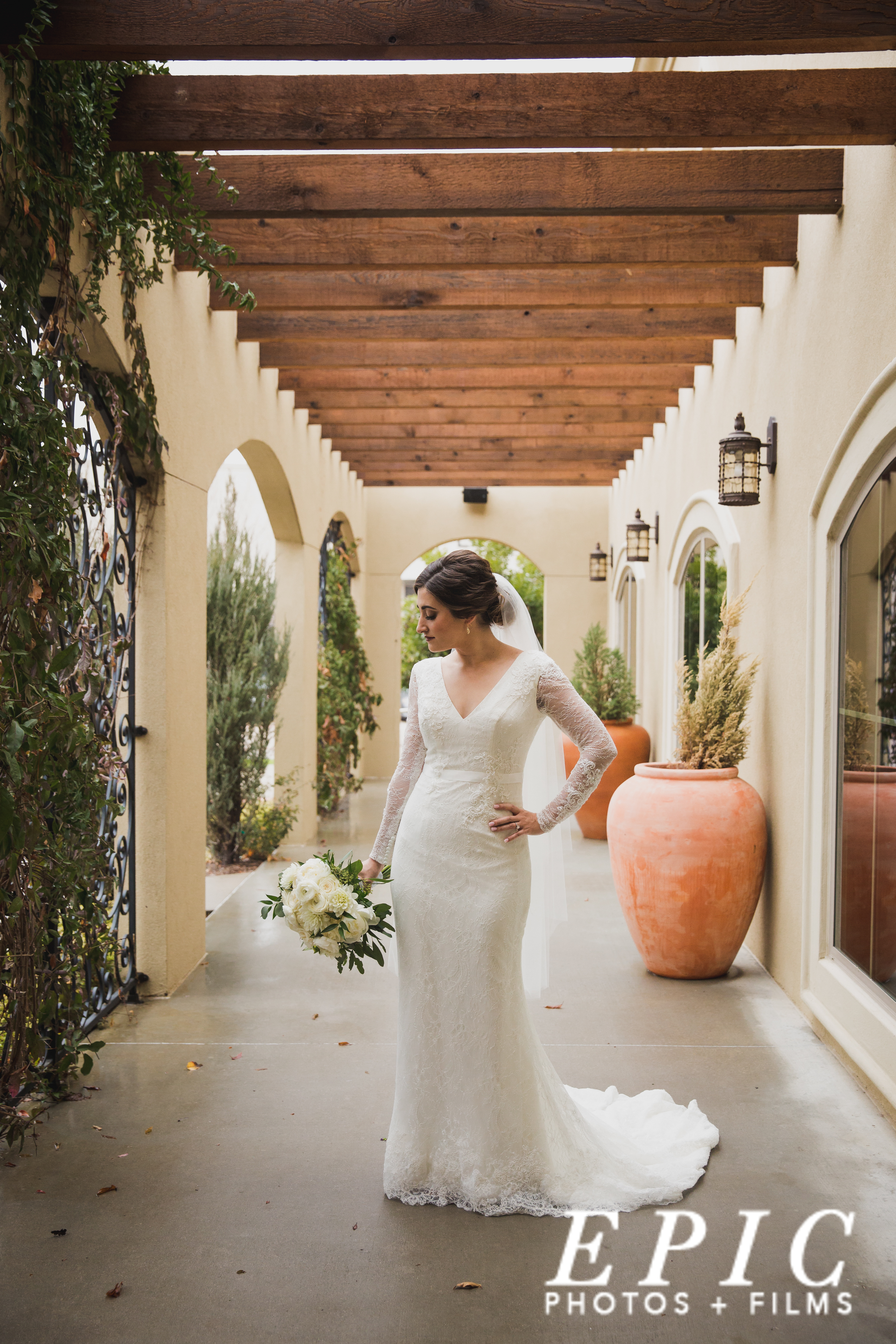 bride posing in her lace, long-sleve wedding gown in a gogeous veranda at the Capel at Ana Villa