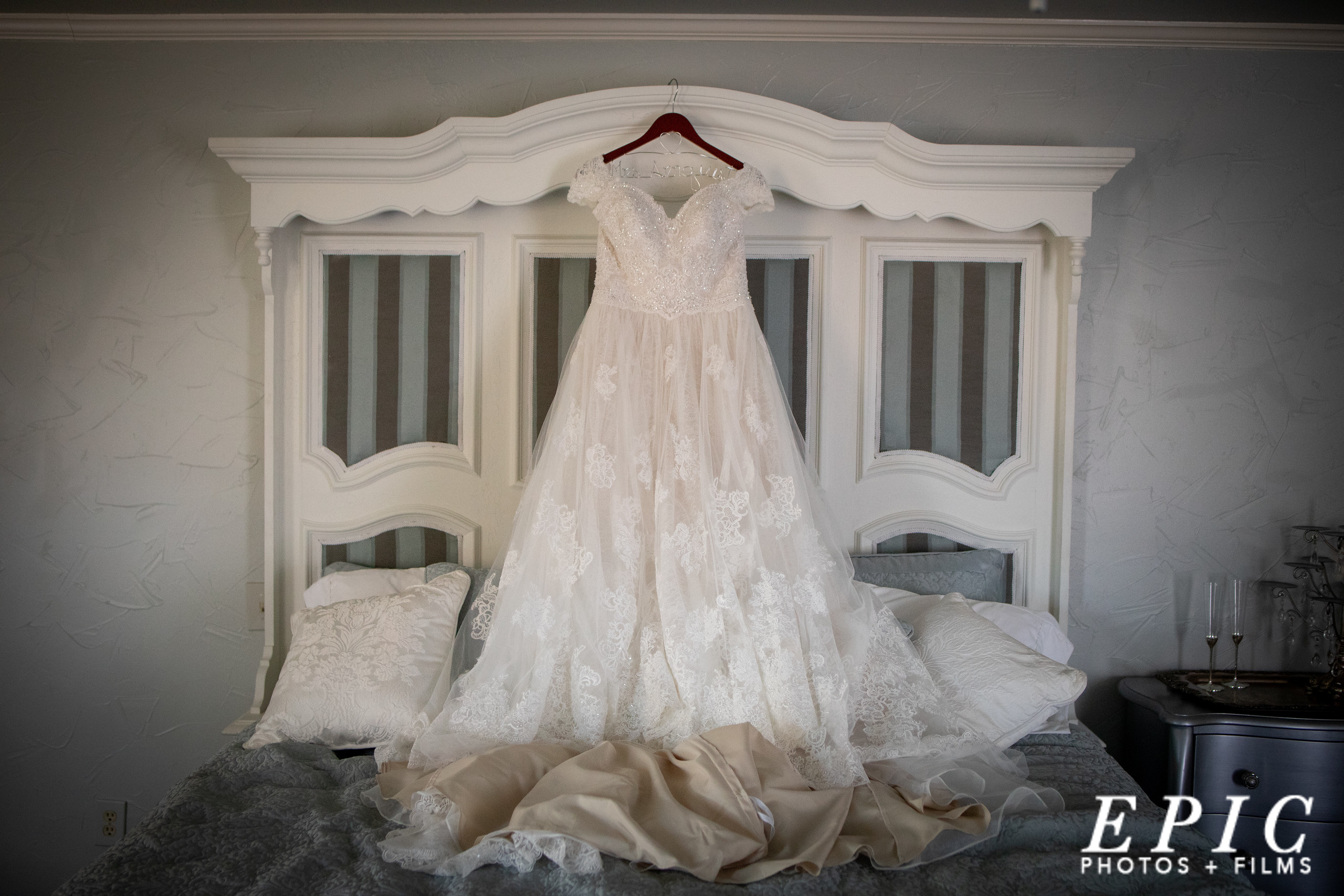 wedding gown hanging on a large white french country style headboard