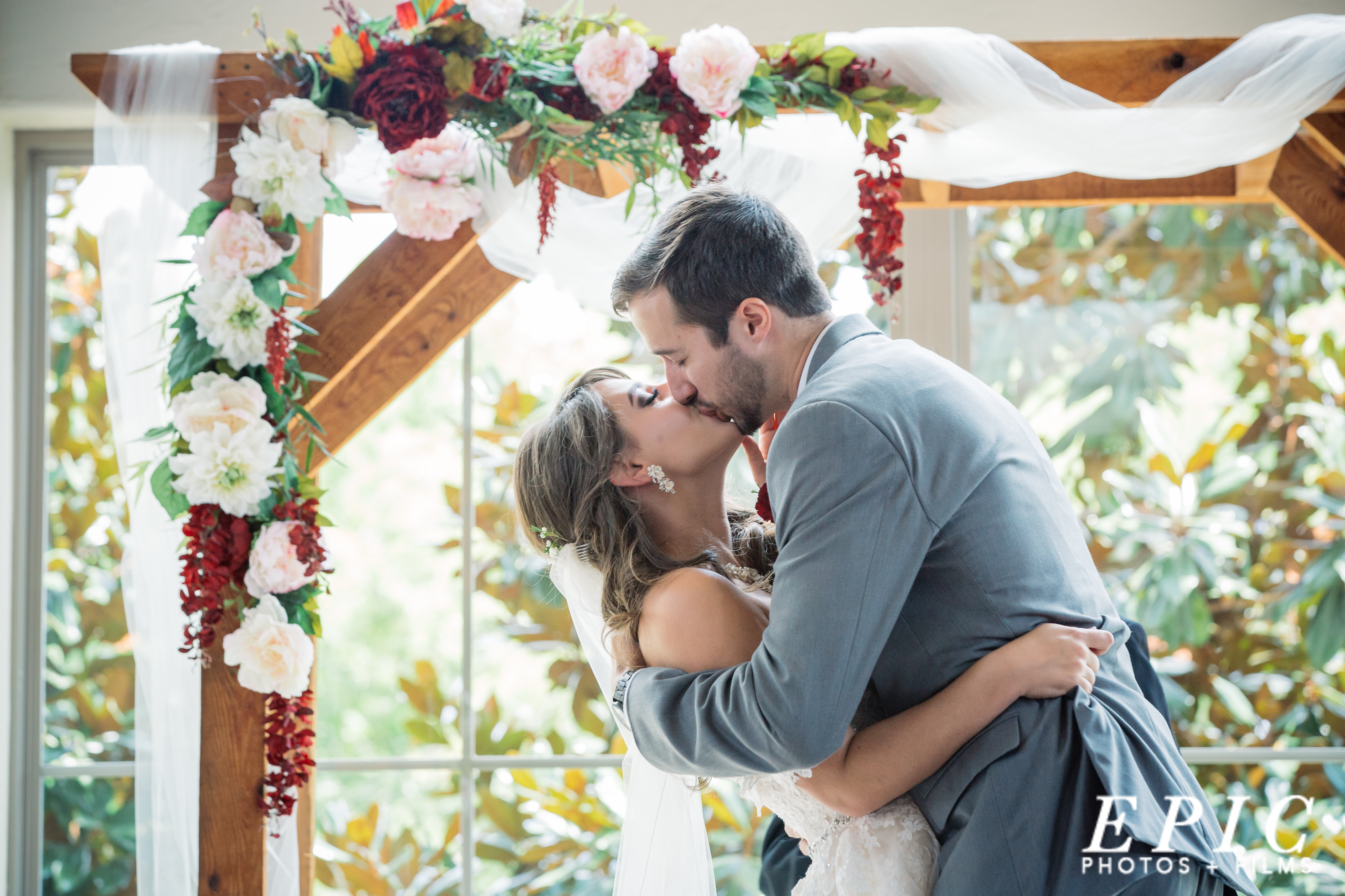 Bride and grrom kiss for the first time as man and wife under a wooden wedding arch covered in large pink and deep red flowers with shear white fabric