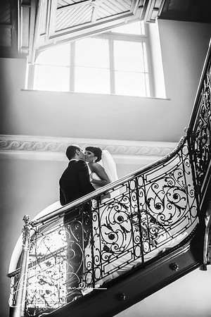 groom and bride is kissing on the background stairs
