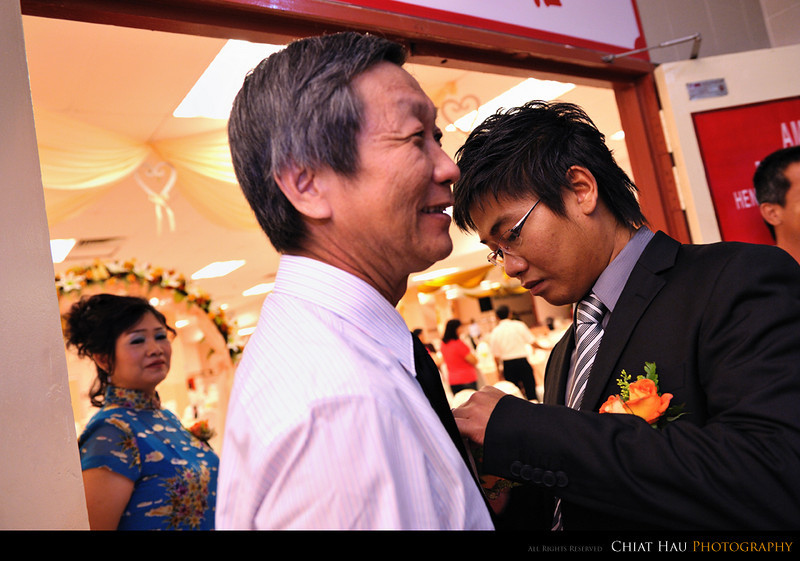 Wei helping dad with the flower pin