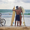 newlywed couple at the beach with surfboards and bikes