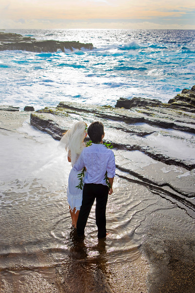 young mixed newlywed couple on lava cliffs by the pacific ocean in Hawaii