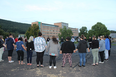 """JOHN E. USALIS/STAFF PHOTOThe clients and staffers at Gaudenzia New Destiny and Gaudenzia                               Fountain Springs hold hands in a circle at the helipad near both facilities at the end of the """"Light Up the Sky"""" recovery event Monday evening."""