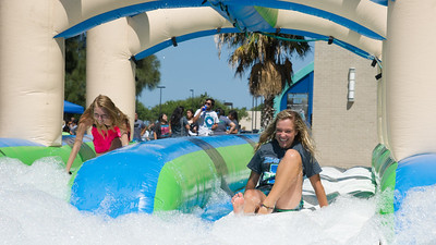 Students race down the slip n slide during Island Bash on the east lawn.