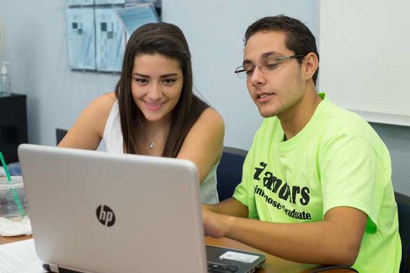 Casa tutor Saira Gonzalez(left) assist student Omar Solis(right) with his business assignment.