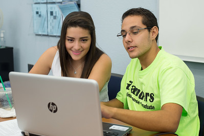 Casa tutor Saira Gonzalez(left) assist student Omar Solis(right) with his business assignment.