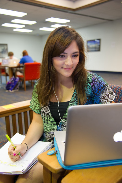 Business student Patty Waters, works on her communication homework in the Mary and Jeff Bell library.