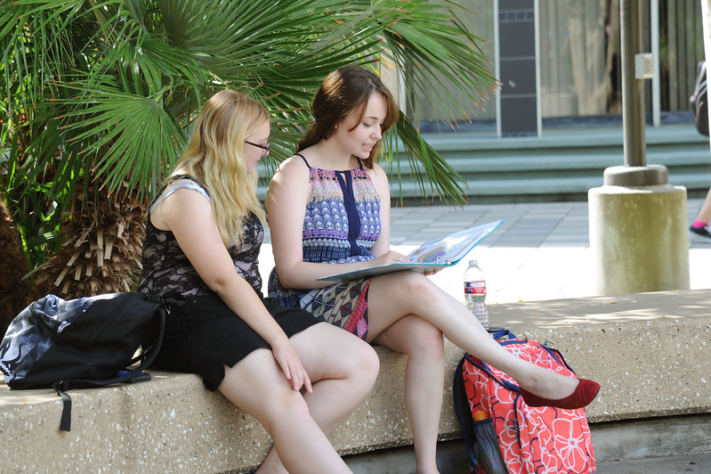 Students Alyssa Lilly(right) and Kaela Mathus(left) study collaboratively for their Biology Class under the shade in Lee Plaza.
