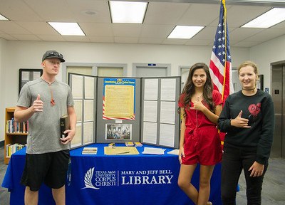 Jacob Cunningham(left) Megan Morsia and Alison Sprosty gather around the Constitution set up at the Mary and Jeff Bell Library.
